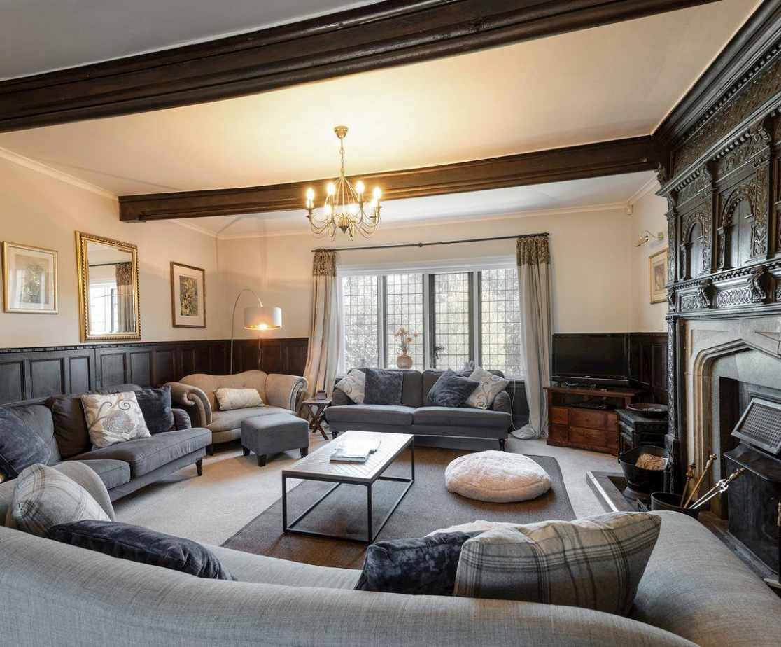 Living room with wood panelling & open fire